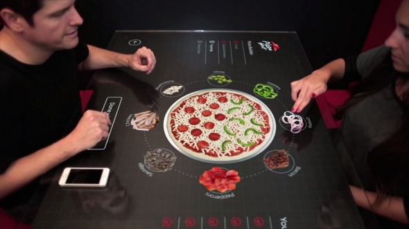 The Interactive Tabletop gives several options such as swiping to change the size of the dough, choosing the sauce, adding toppings.