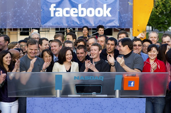 Mark Zuckerberg, chief executive officer of Facebook Inc., center, Sheryl Sandberg, chief operating officer of Facebook, center left, after remotely ring the opening bell for trading at the Nasdaq MarketSite from the Facebook campus in Menlo Park, California, U.S