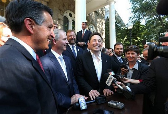 Tesla Motors CEO Elon Musk, right, and Nevada Gov. Brian Sandoval, extreme left, at a press conference where Nevada was announced as the new site for a $5 billion car battery gigafactory, at the Capitol in Carson City, Nev., on Thursday, Sept. 4, 2014